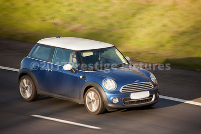 Blue Mini Cooper driving on a motorway