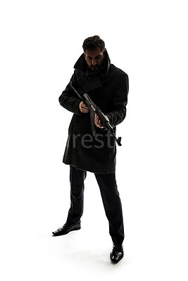 A semi-silhouette of a mystery man in a big coat, holding an AK-47 – shot from eye level.