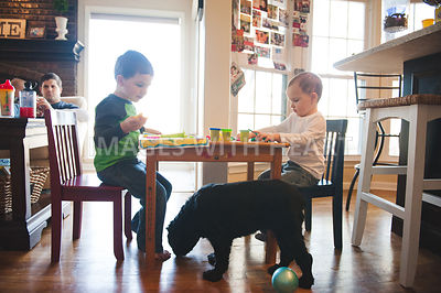 children with art project at table and dog