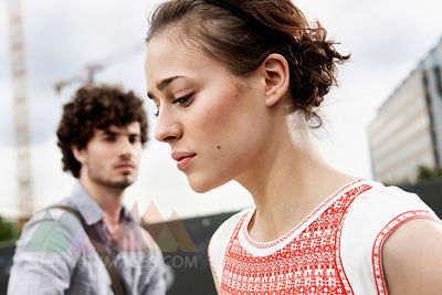 Germany, Berlin, Young couple, woman looking down, side view, portrait, close-up