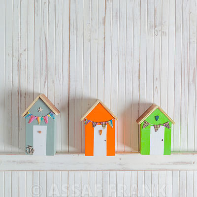 Tiny beach huts on wooden background