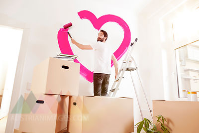 Young man painting a pink heart on a wall in new apartment