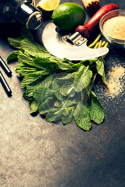 Mojito cocktail ingredients (fresh mint, lime) on rustic background