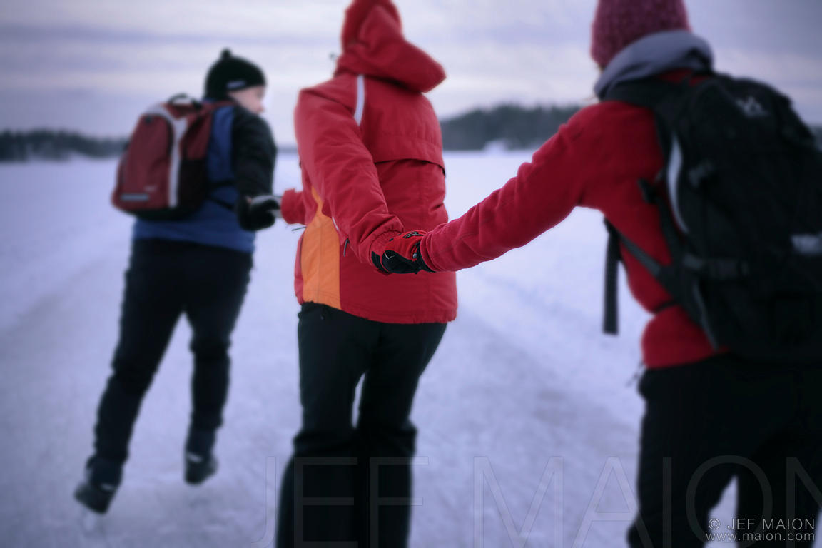 Ice-skaters hand-in-hand on frozen lake