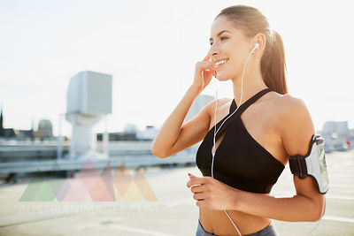 Smiling young woman wearing earphones preparing to work out in the city