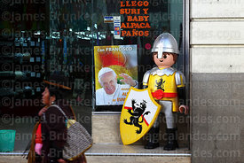 Aymara woman walking past poster for visit of Pope Francis in shop window, La Paz, Bolivia