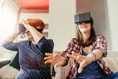 Adult daughter with mother at home wearing VR glasses