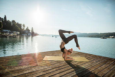 Woman practicing yoga on jetty at a lake