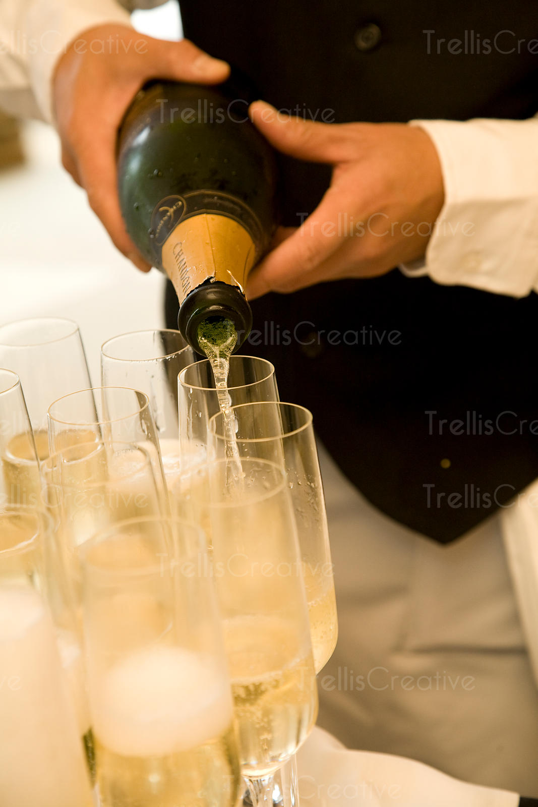 A waiter pours glasses of white sparkling wine