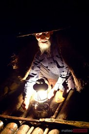 Chinese fisherman with lantern at night, near Guilin, China