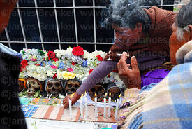 Women smoking as they sit next to skulls, Ñatitas festival, La Paz, Bolivia
