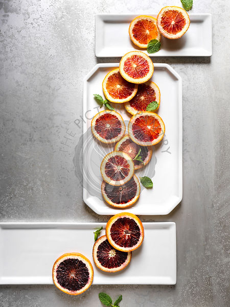 Blood orange slices layed out in artistic shape over white plates and textured metal surface.