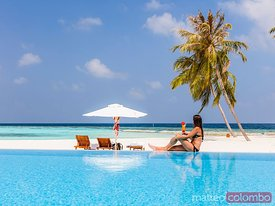 Woman with drink relaxing by the swimming pool, Maldives