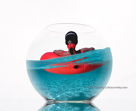fishbowl with composite of woman on red tube float inside