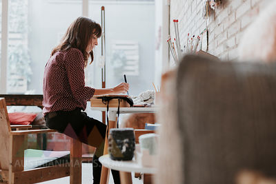 Woman sitting in studio taking notes