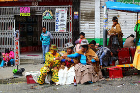 A ch'uta and cholitas drinking beer during parades for the Entierro del Pepino, La Paz, Bolivia