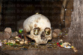 Skull with coin offerings in eye sockets in catacombs of church of Santiago the Apostle / Immaculate Conception, Lampa, Peru