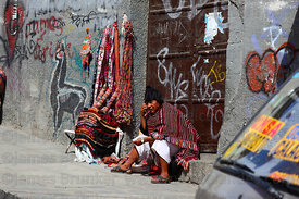 Quechua man from Tarabuco talking on mobile phone while sitting next to his textile stall in street , La Paz , Bolivia