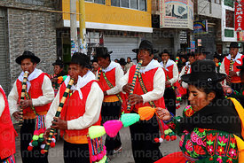 Musicians playing lawa k'umu flutes (a type of pinkillo) accompanying chacareros dancers from Acora village, Virgen de la Candelaria festival, Puno, Peru
