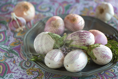plated white aubergines with purple fine stripes, onion and garlic against purple floral tablecloth