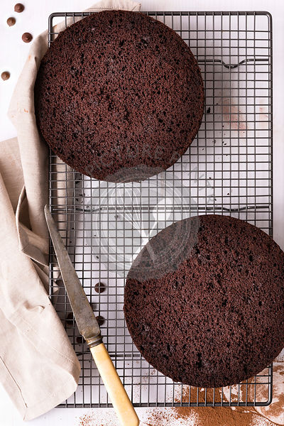 Round chocolate cake cut in two halves cooling on a wire cake rack.