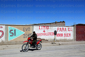 Policeman riding past propaganda showing support for Evo Morales and the industrialisation of the Salar de Uyuni's lithium reserves, Colchani, Bolivia