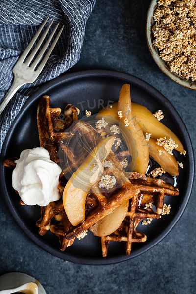 Waffles on plate with pears and whipped cream
