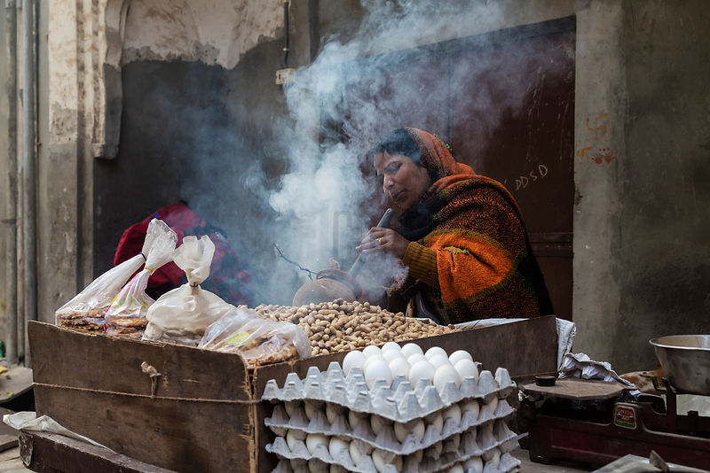 Woman Worming Coals in a Clay Pot to Roast Peanuts