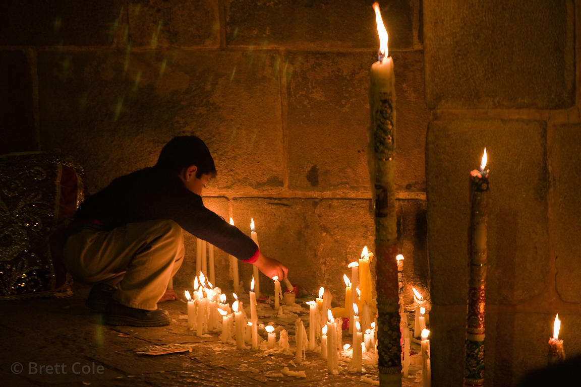 A boy lights candles during the Festival of Lights religious ceremony in Cusco, Peru