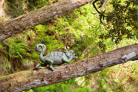 Bronze chameleon sculpture on tree branch