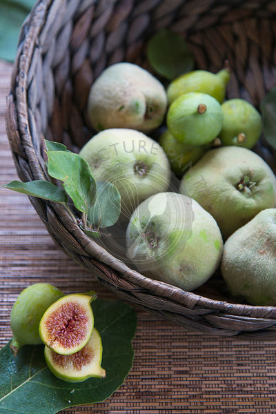 quinces and figs in woven basket with cut figs in foreground