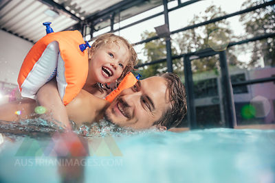 Happy father with daughter in indoor swimming pool