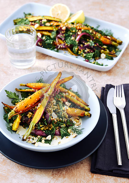 Roasted heirloom carrots,  cooked freekeh grain, roasted red onions, kale, parsley, dill, maple syrup and orange dressing with zatar. And a yogurt sauce. topped off with roasted hazel nuts.