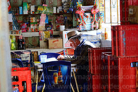 Man doing paperwork in his shop, Juli, Puno Region, Peru