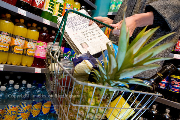 Woman with a shopping basket in a supermarket in Birmingham, West Midlands,