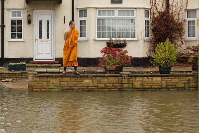 Buddhist Monk Balancing on Garden Wall Avoiding Flood Waters