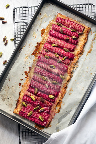 A rhubarb and pistachio nut tart cooling on a baking tray.