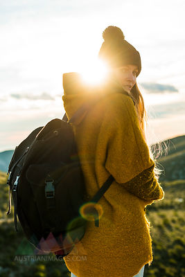 Portrait of young woman with backpack in nature at sunset