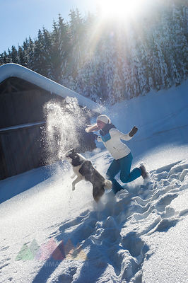 Austria, Altenmarkt-Zauchensee, happy young woman playing with dog in snow