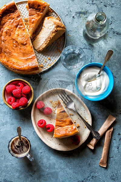 Sliced cheesecake served with raspberries and crème fraiche