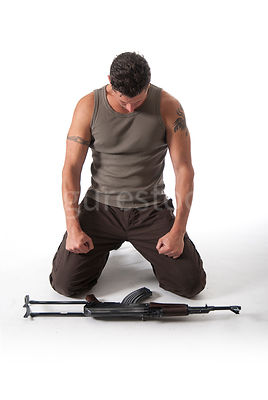 A man in a kneeling with an AK-47 in front of him – shot from mid level.