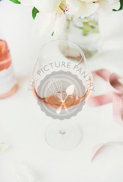 Rose wine in glass, pink ribbon, peony flowers