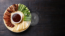 Sliced Peking Duck served with fresh cucumber, green onions, cilantro and roasted wheaten chinese pancakes with Hoysin sauce on black wooden background copy space
