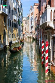 Gondolas with tourists in a calan of Venice, Italy