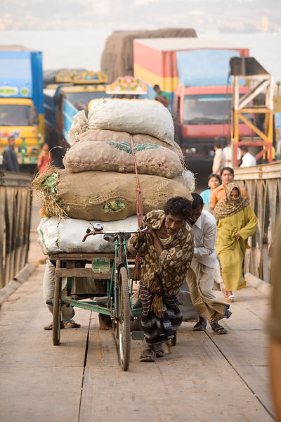Bangladesh - Chittagong - A rickshaw driver pulls his heavy load up the gangplank after disembarking from a ferry on the southern shore of the Karnaphuli River