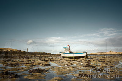 Fishing boat at low tide and ile Vierge lighthouse