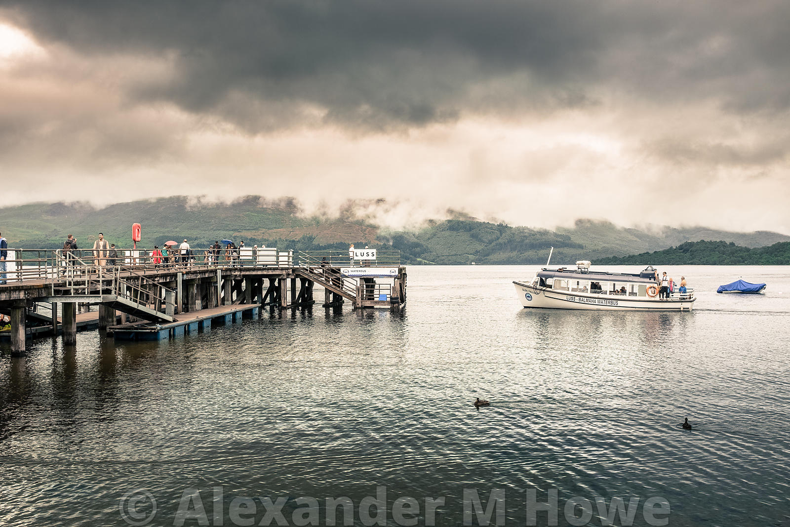 The Glen Falloch pleasure boat approaching the Luss pier on a heavily overcast day on Loch Lomond