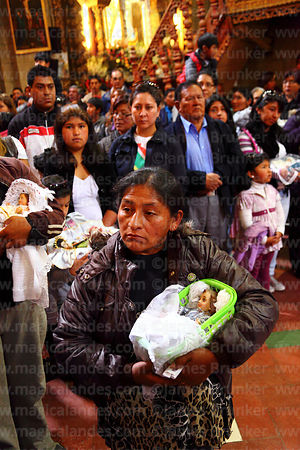 People holding baby Jesus figures in church during mass for Reyes (Epiphany, January 6th), La Paz, Bolivia