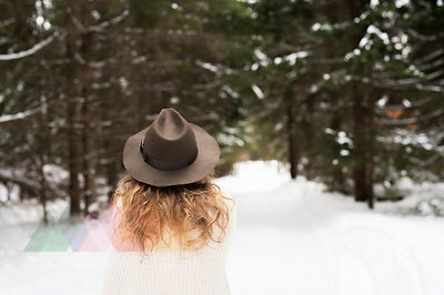 Back view of young woman wearing hat and knit pullover in winter forest