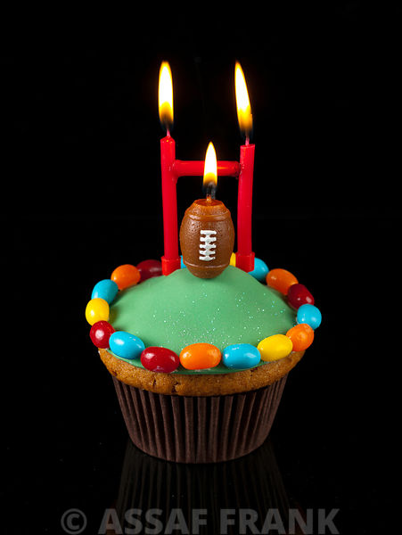 Cupcake with rugby ball shaped candle